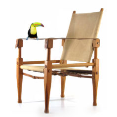 Wilhelm Kienzle 1928 vintage Safari chair. Oak, bronze fittings and linnen. A real eye catcher for your interior. In great condition. Designed by Wilhelm Kienzle in 1928 for Wohnbedarf. Wilhelm Kienzle worked in 1914 with Peter Behrens at AEG in Berlin. Taught at the Zurich School of Design from 1916 to 1951 Dimensions: 87,5 cm height, depth 63 cm, width 56,5 cm.
